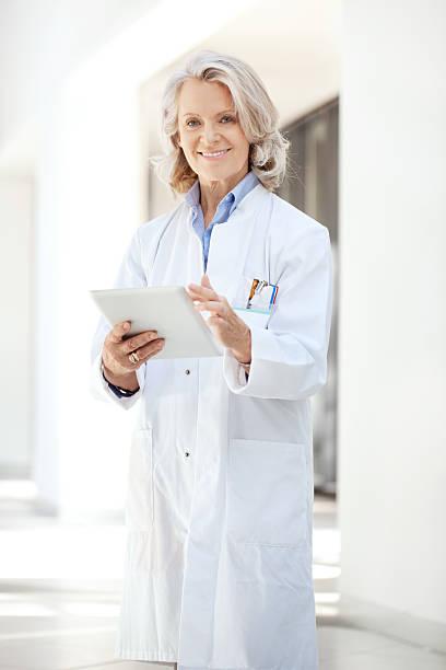 arzt im krankenhaus mit digitalen tablet - alvarez stock-fotos und bilder