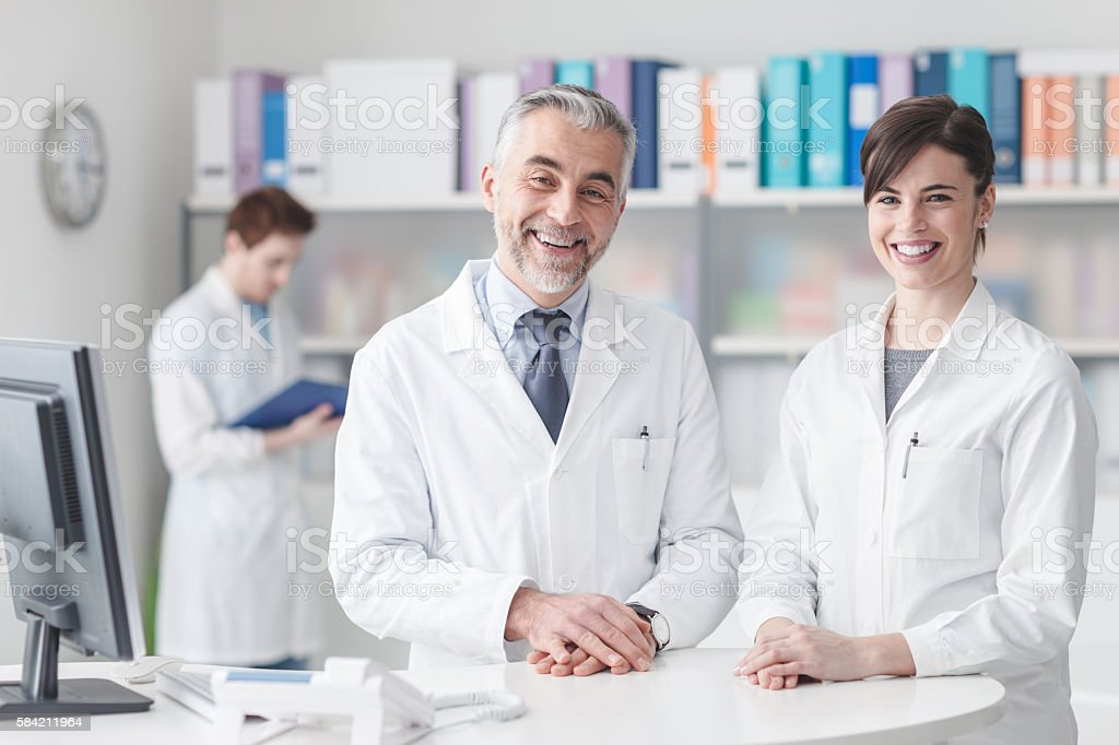 Doctor at the reception desk with his assistant stock photo
