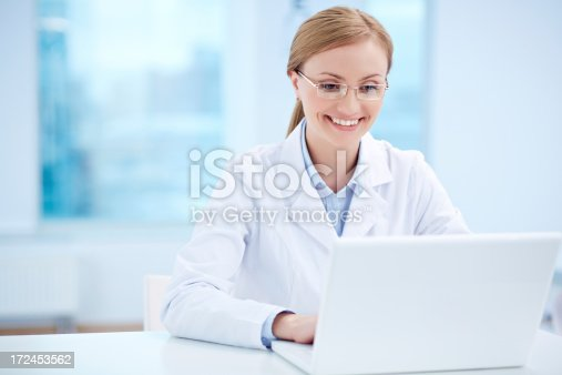 Successful doctor in glasses working on laptop