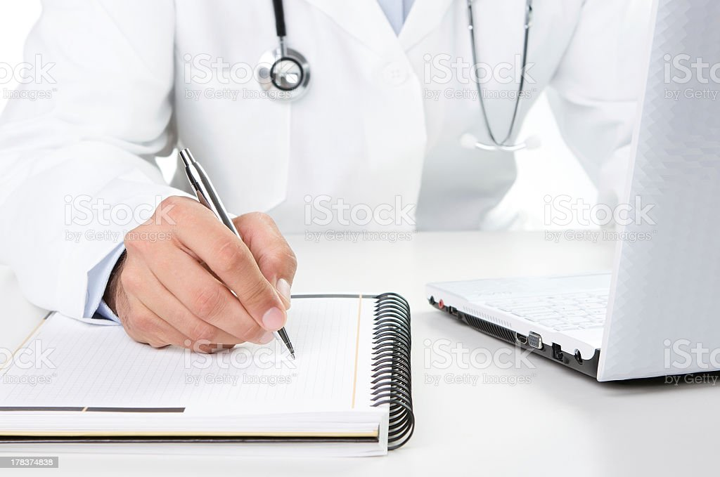 A doctor at work with a notebook and a pen royalty-free stock photo