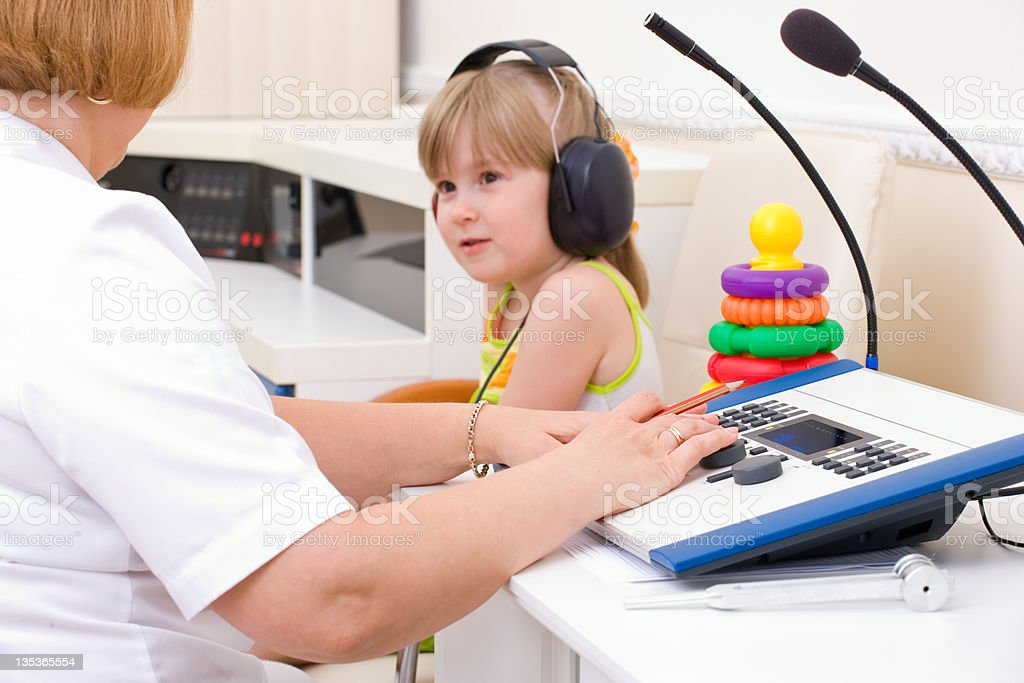 Doctor audiologist testing girl stock photo