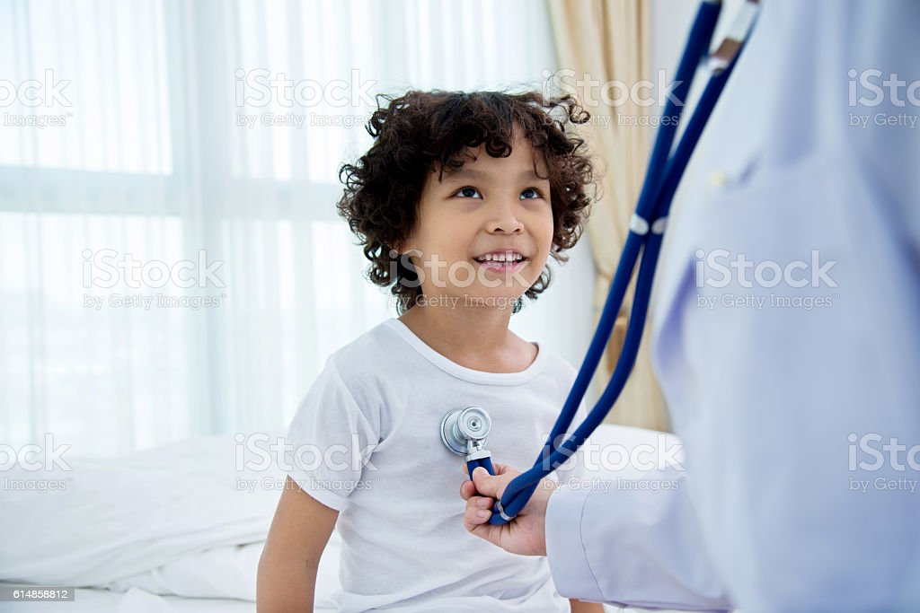 Doctor auscultating a little boy with stethoscope stock photo