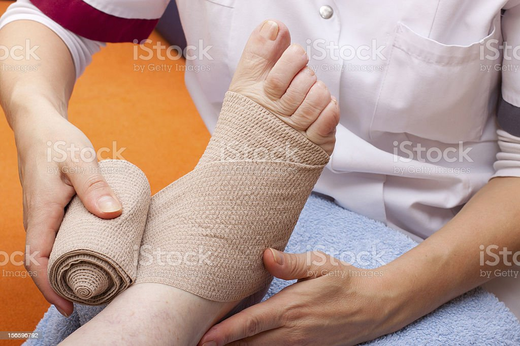 Doctor bandaged foot of a patient royalty-free stock photo