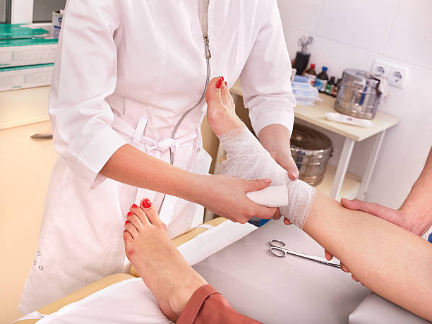 Doctor bandaging patient in hospital stock photo