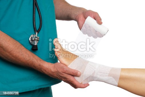 istock Doctor Bandaging Woman Ankle 184330739