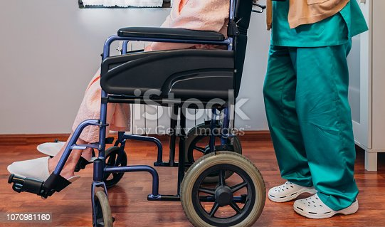 Female doctor carrying elderly female patient in a wheelchair