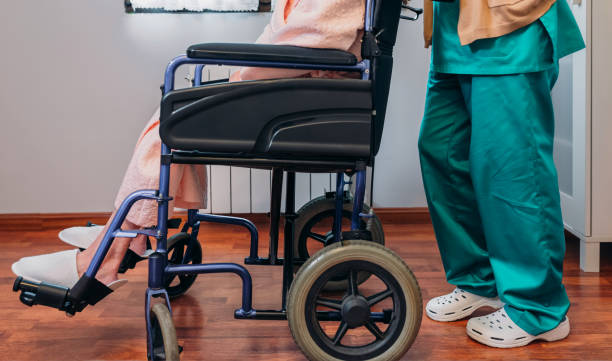 Doctor carrying elderly patient in a wheelchair Female doctor carrying elderly female patient in a wheelchair paralysis stock pictures, royalty-free photos & images