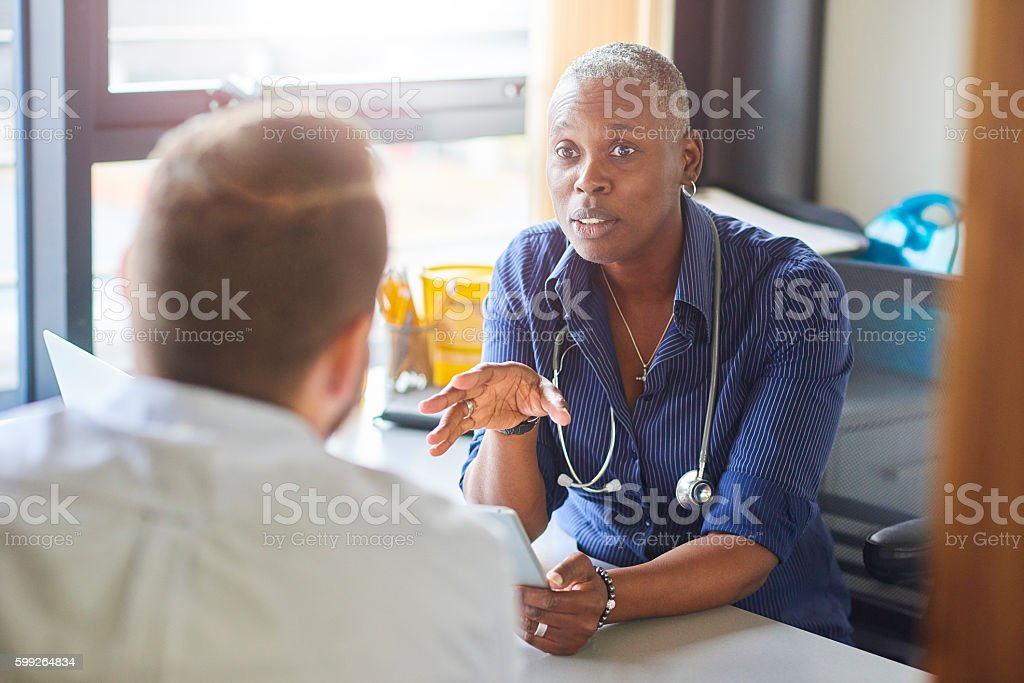 Doctor chatting to male patient – Foto