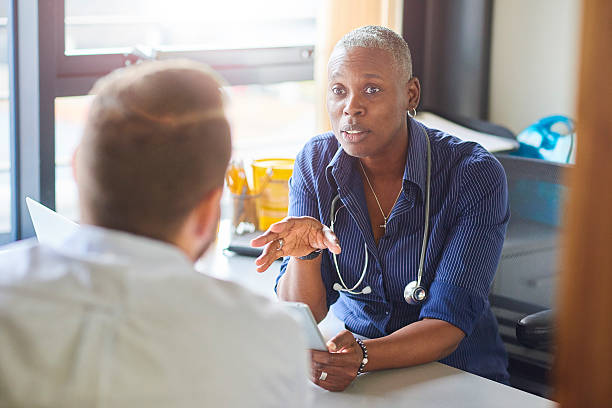 Doctor chatting to male patient stock photo
