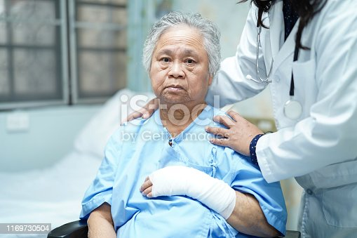 1133511905istockphoto Doctor check hand with bandage on wheelchair, Asian senior or elderly old lady woman patient accident in nursing hospital ward : healthy strong medical concept. 1169730504