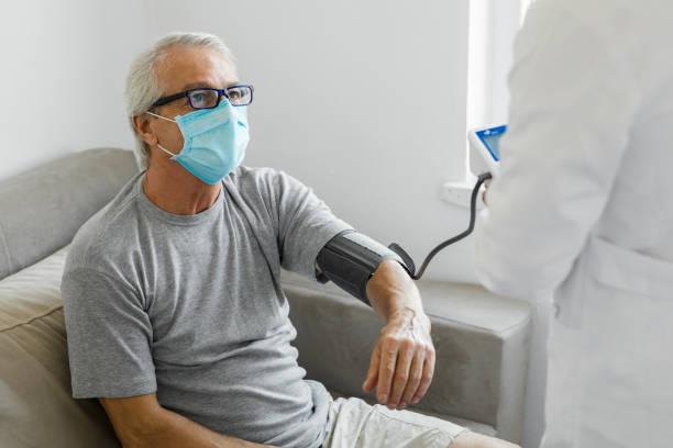 Doctor check up senior man at home stock photo