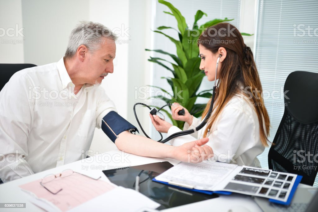 Doctor checking a patient blood pressure stock photo