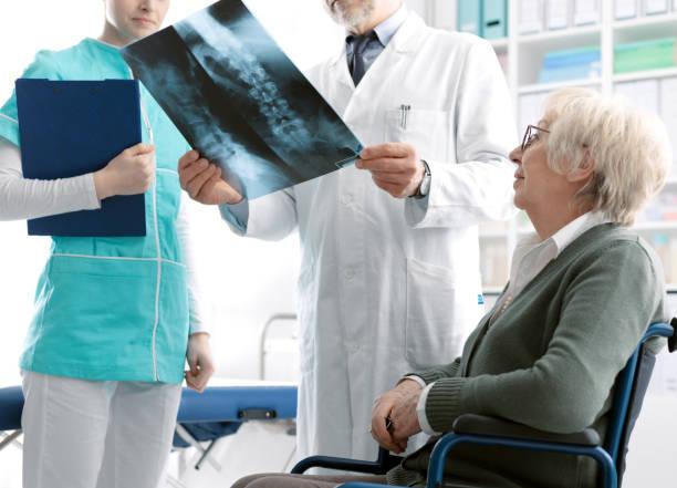 Arzt prüft Röntgenbild einer älteren Patientin bei einem Krankenhausbesuch, Verletzung und Osteoporose-Konzept – Foto