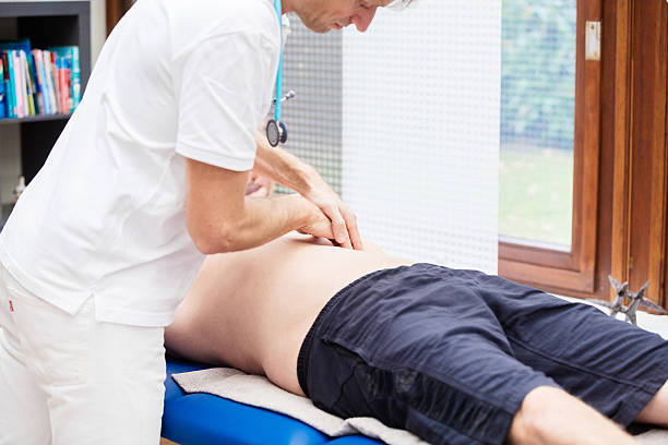 Doctor checking abdomen of mature patient stock photo
