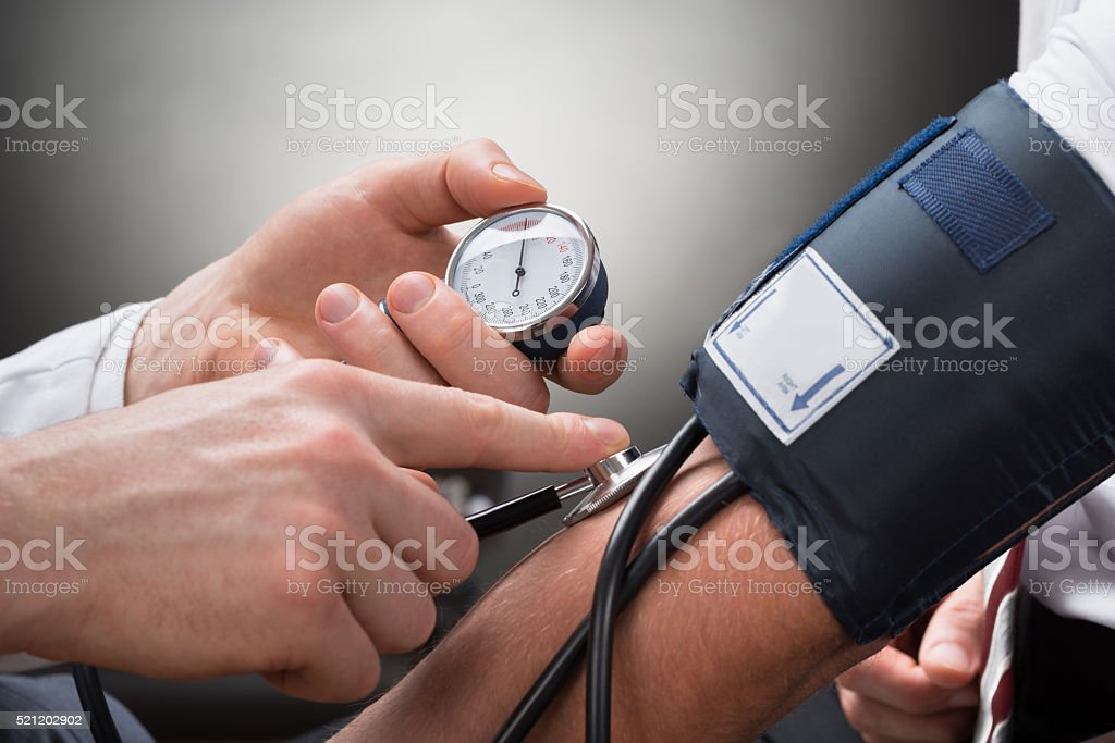 Doctor Checking Blood Pressure Of A Patient stock photo