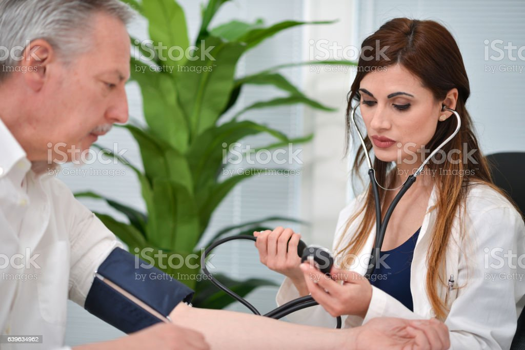 Doctor checking blood pressure stock photo