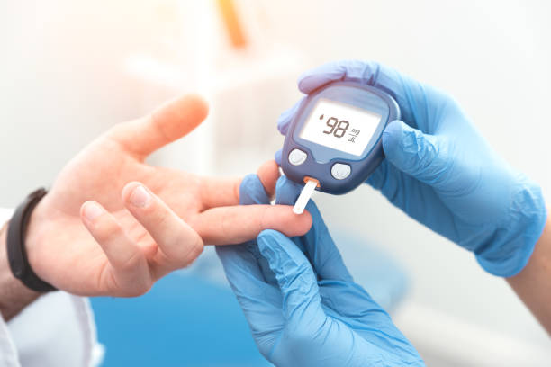 doctor checking blood sugar level with glucometer - diabetes стоковые фото и изображения