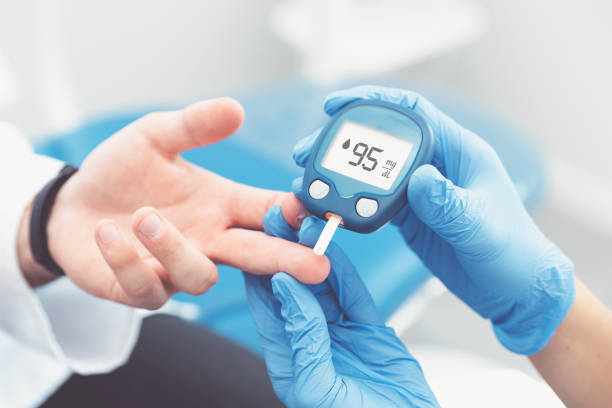 Doctor checking blood sugar level with glucometer stock photo