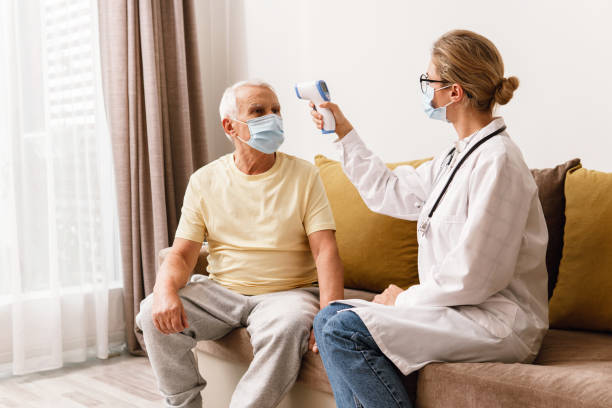 Doctor checking body temperature to elderly man during home visit stock photo