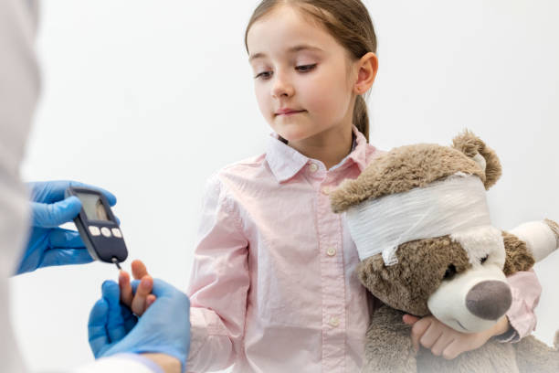 Doctor checking diabetics on equipment of girl with teddybear at clinic stock photo