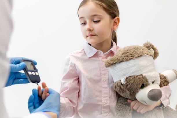 Arzt überprüft Diabetiker auf Ausrüstung von Mädchen mit Teddybär in Klinik – Foto