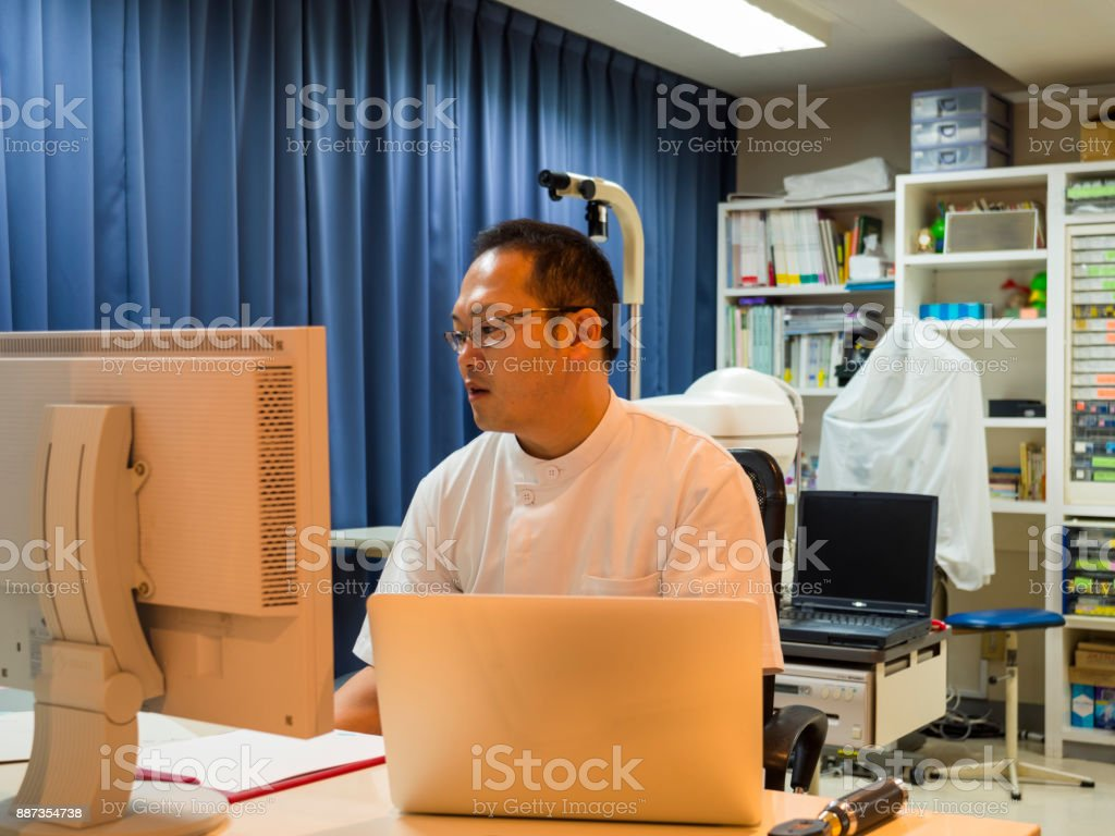 Doctor checking information using computer. stock photo