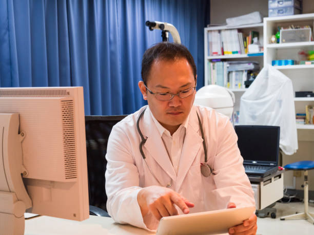 Doctor checking information using tablet. stock photo