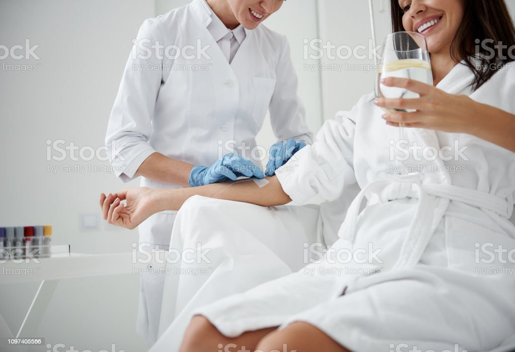 Doctor checking intravenous drip on lady hand while she drinking water stock photo