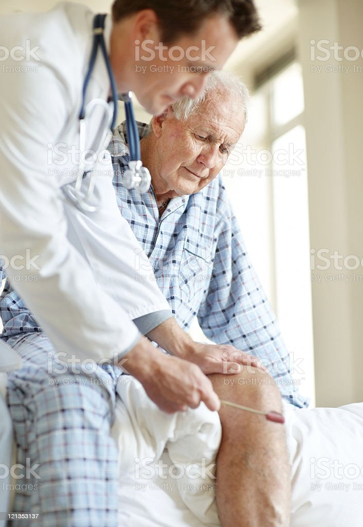 Doctor checking old man knee using a reflex hammer royalty-free stock photo