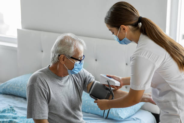 Doctor checking patient's blood pressure at home stock photo