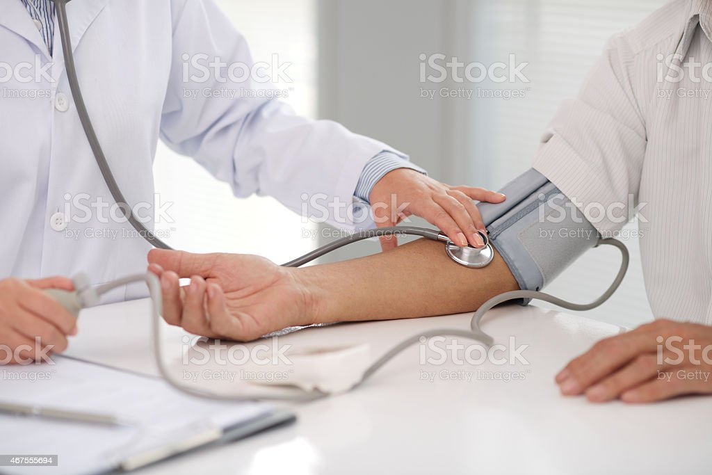 Doctor checking patients blood pressure on right arm stock photo