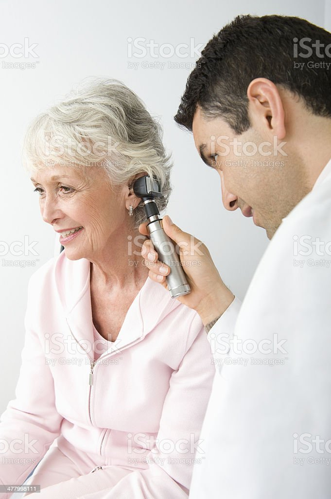 Doctor Checking Patient's Ear Using Otoscope In Clinic stock photo