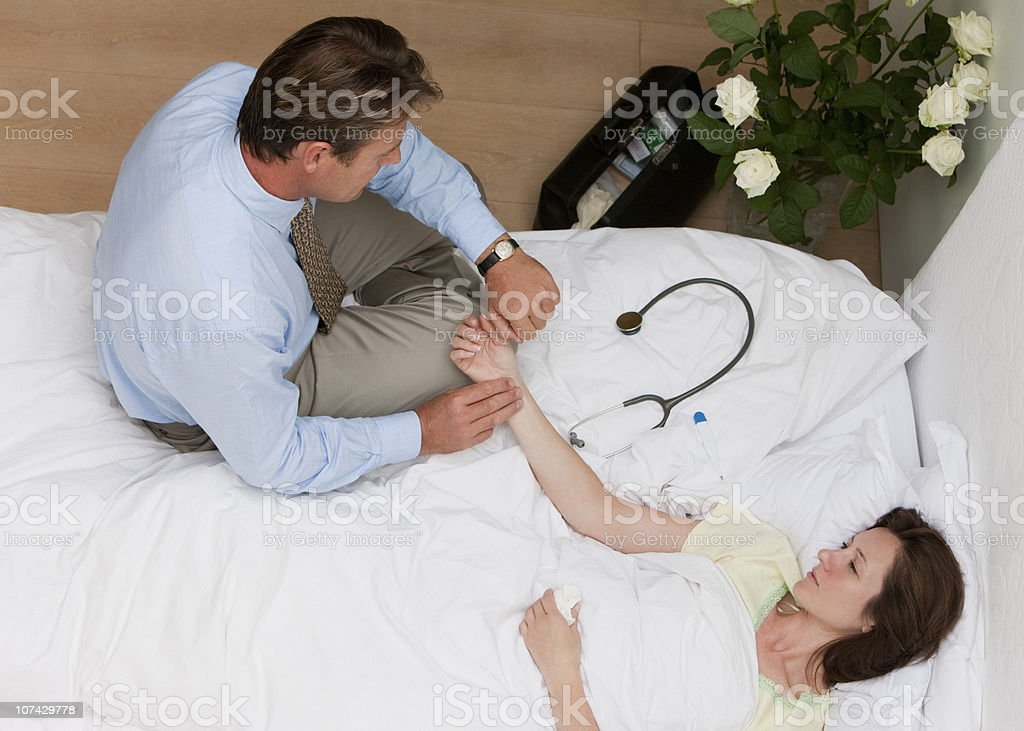 Doctor checking patients pulse on house call royalty-free stock photo