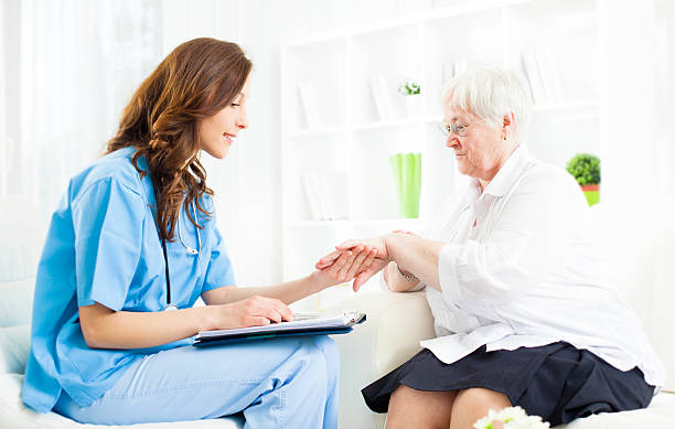 Doctor Checking Psoriasis on Senior Woman patient hand. Young female doctor examining psoriasis on hand of an senior woman patient in a doctor's office. Could be used also as Homeopathy Interview. Selective focus to senior woman. psoriasis stock pictures, royalty-free photos & images