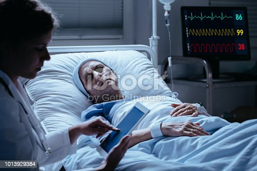 928968772 istock photo Doctor checking sick senior patient's results on the tablet 1013929384