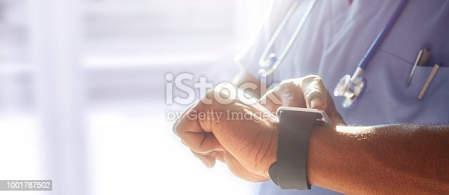 Doctor or surgeon stood in hospital ward using smart watch technology