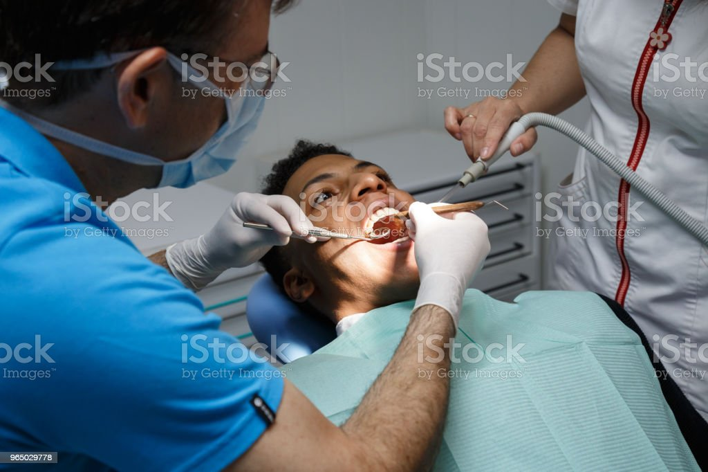 Doctor checking teeth of black man royalty-free stock photo