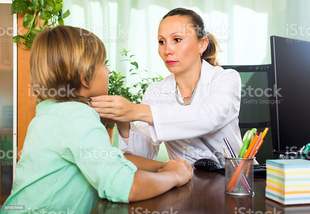 Doctor checking thyroid of teenager stock photo