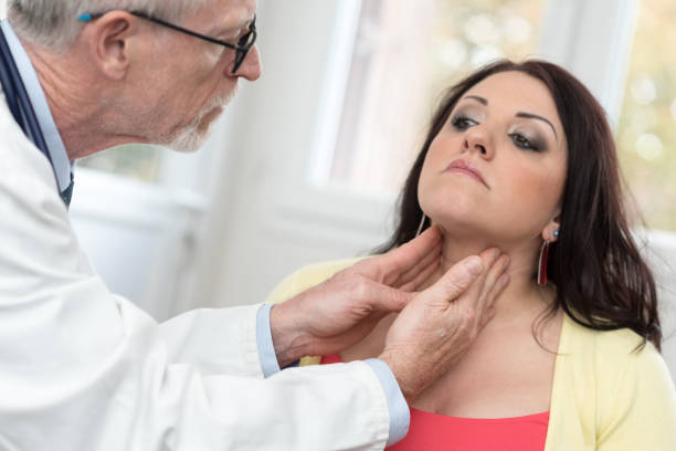 Doctor checking thyroid Doctor checking thyroid of a young patient endocrine system stock pictures, royalty-free photos & images