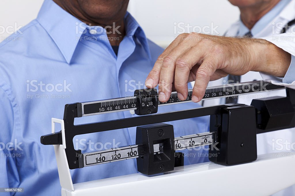 Doctor Checking Weight royalty-free stock photo