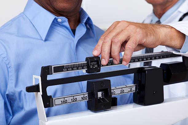 doctor checking weight - scale stock photos and pictures