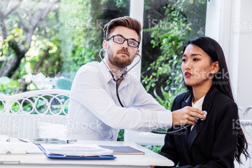 Doctor checking woman patient's breath sound with a stethoscope stock photo