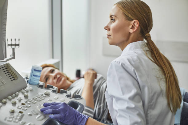 Doctor checking woman pregnancy during sonography procedure stock photo