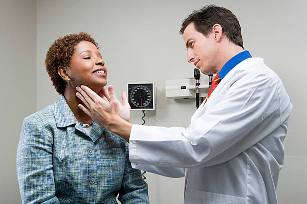 Doctor checking womans throat Doctor checking woman's throat human gland stock pictures, royalty-free photos & images