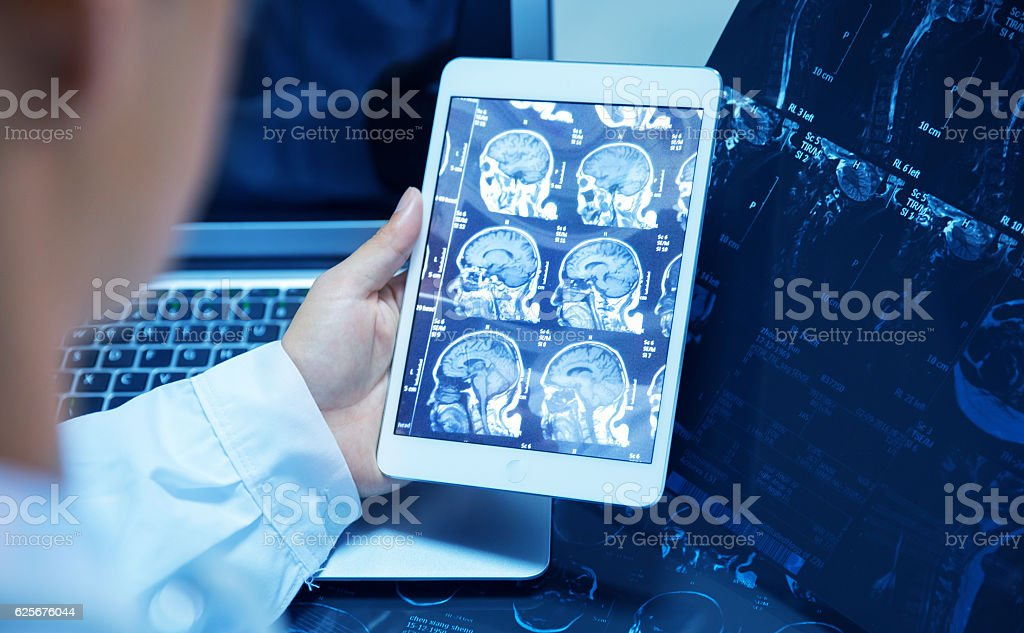 doctor checking x ray with tablet stock photo