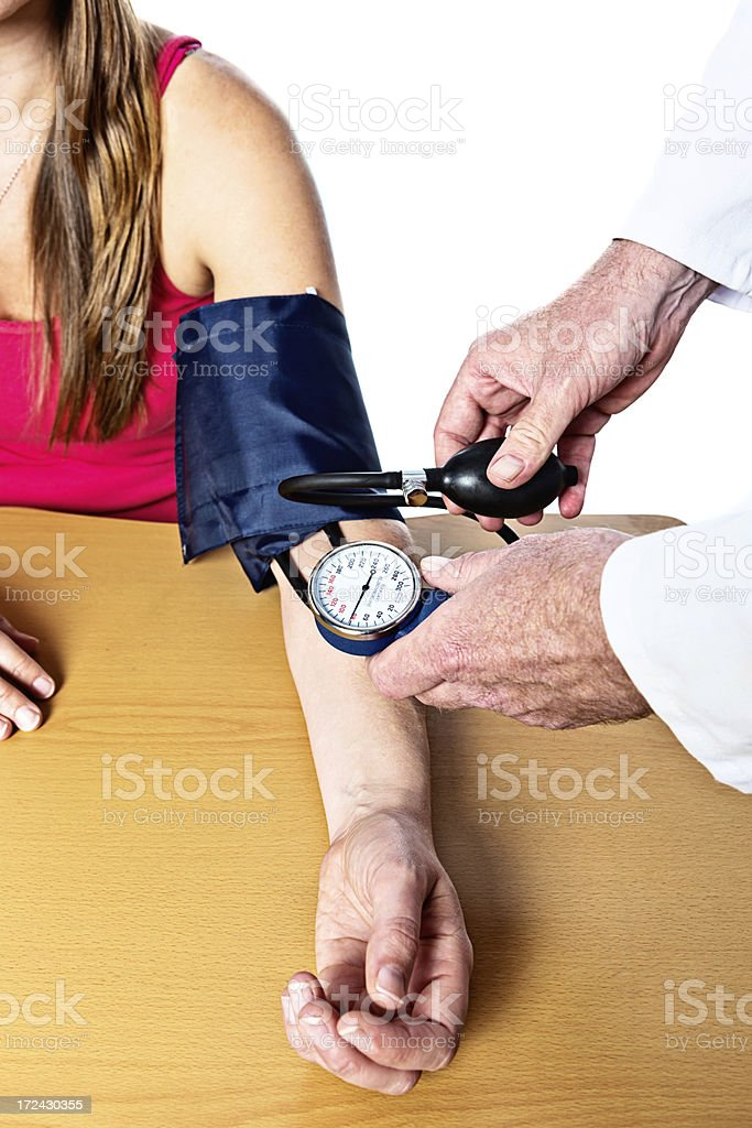 Doctor checking young woman's blood pressure reading royalty-free stock photo