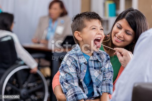 istock Doctor checks young patient's throat during exam 638552050