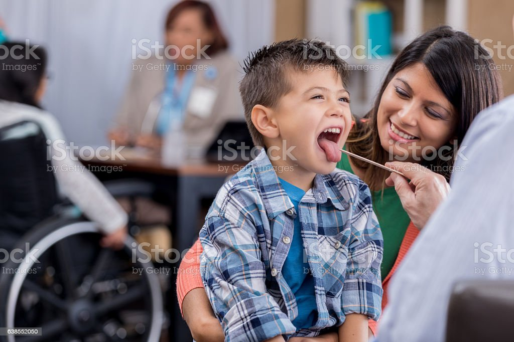 Doctor checks young patient's throat during exam stock photo