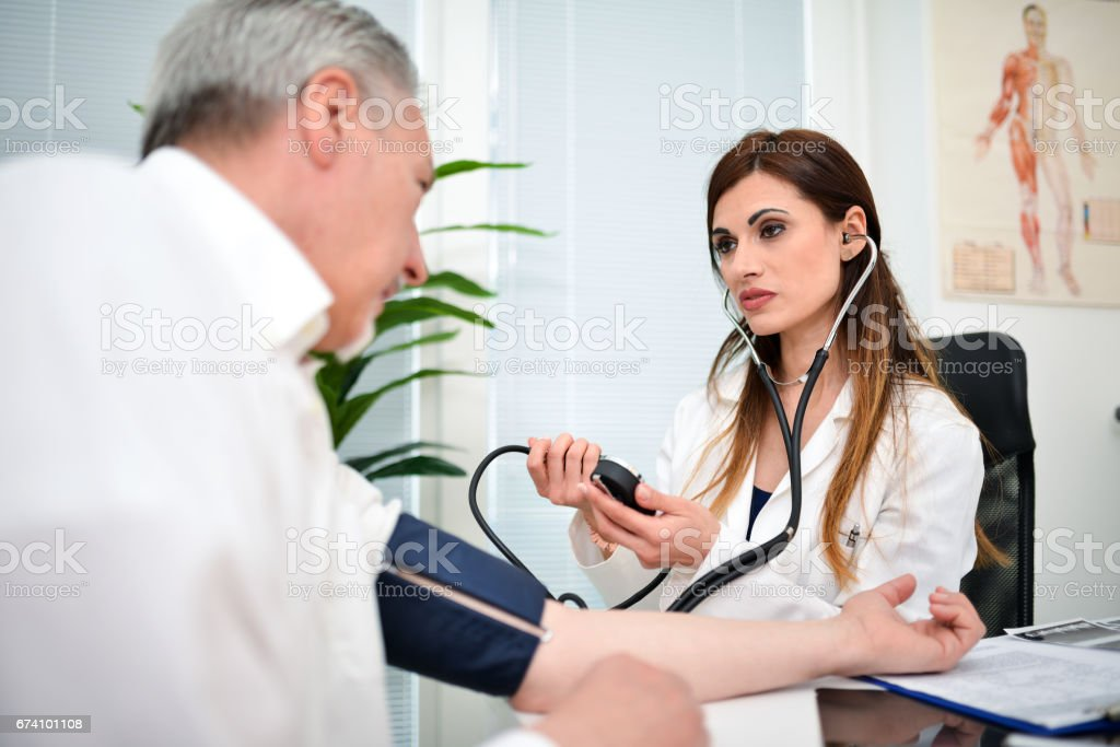 Doctor cheking a patient blood pressure royalty-free stock photo