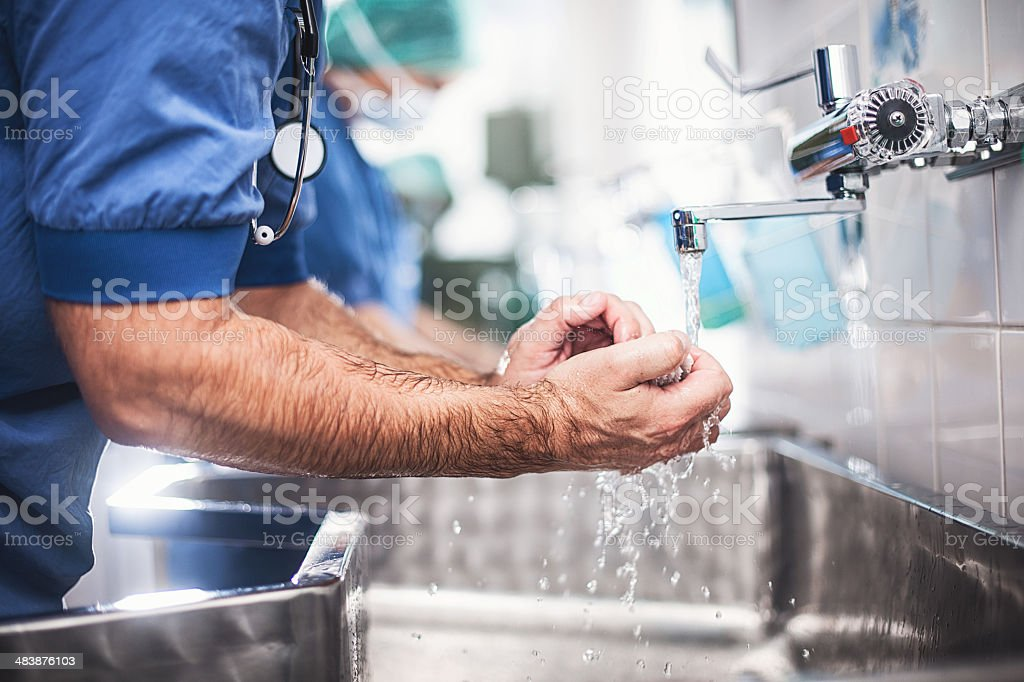 Doctor cleaning hands stock photo